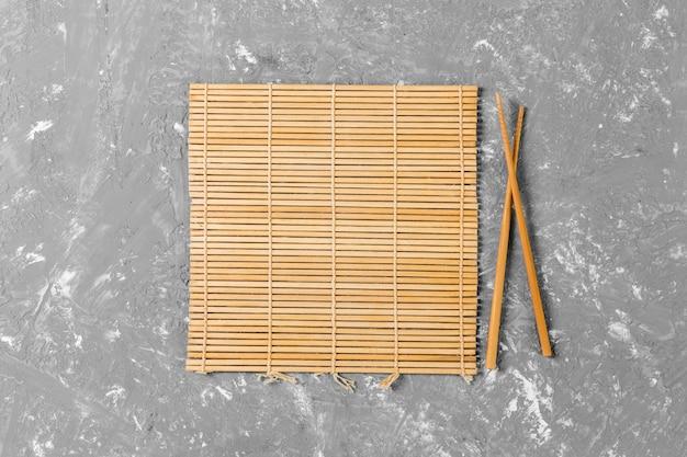 Due bastoncini di sushi con stuoia di bambù marrone vuota o piastra di legno su sfondo di cemento Foto Premium