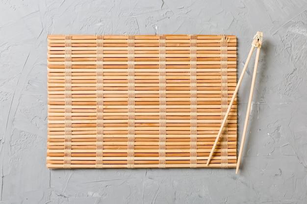 Due bastoncini per sushi con tappetino di bambù vuoto Foto Premium