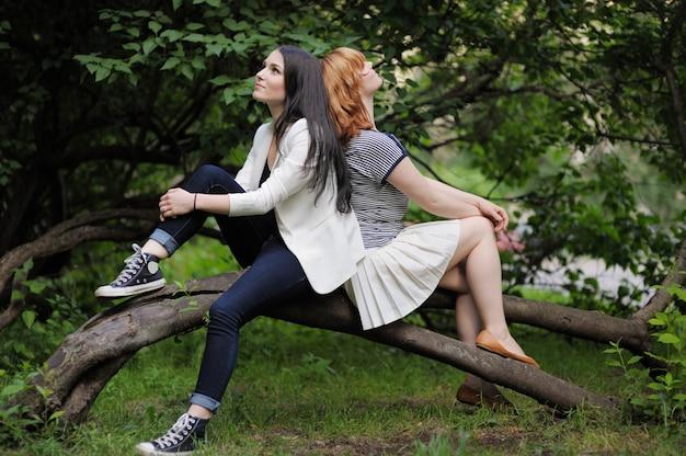 Due bella giovane donna seduta sull'albero Foto Premium