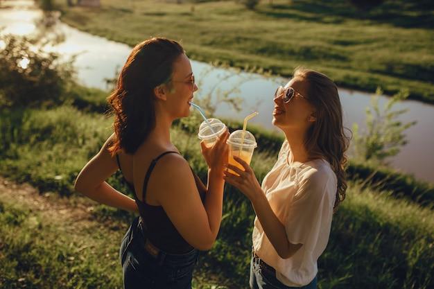 Due belle amiche bevono un cocktail, vestite in maglietta in bianco e nero, si divertono in estate, al tramonto, espressione facciale positiva, all'aperto Foto Premium