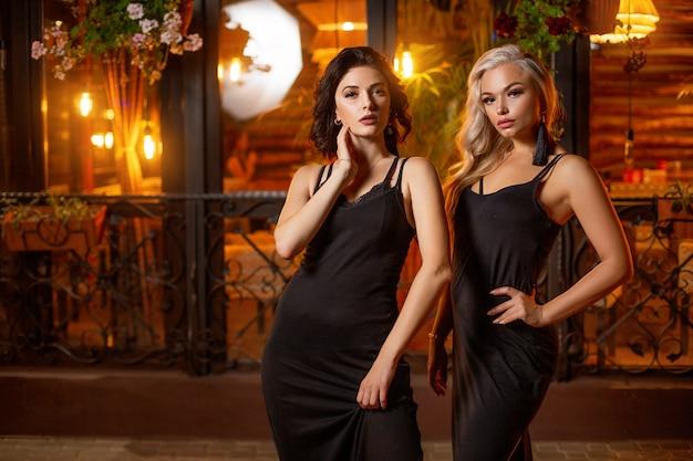 Due belle donne la sera per strada in posa, atmosfera festosa. Foto Premium