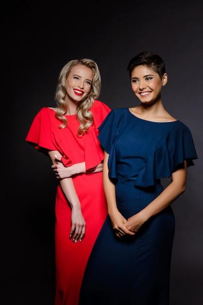 Due belle donne nel sorridere degli abiti da sera Foto Gratuite