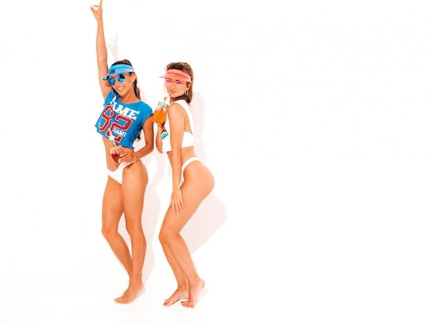 Due belle donne sexy sorridenti in mutande ed argomento bianchi di estate. ragazze alla moda in occhiali da sole, visiera trasparente. impazzendo. modelli divertenti isolati. bere cocktail fresco bevanda liscia Foto Gratuite