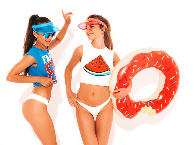 Due belle donne sexy sorridenti in mutande ed argomento bianchi di estate. ragazze in occhiali da sole, visiera trasparente. modelli positivi che si divertono con il materasso gonfiabile a ciambella lilo. isolato Foto Gratuite