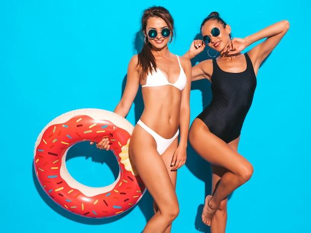 Due belle donne sorridenti sexy in costume da bagno bianco e nero estate costumi da bagno. ragazza in occhiali da sole. modelli positivi che si divertono con il materasso gonfiabile di ciambella lilo. isolato sulla parete blu Foto Gratuite