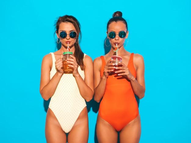 Due belle donne sorridenti sexy in costumi da bagno colorati costumi da bagno estate. ragazze alla moda in occhiali da sole. impazzendo. modelli divertenti isolati. bere cocktail fresco bevanda liscia Foto Gratuite