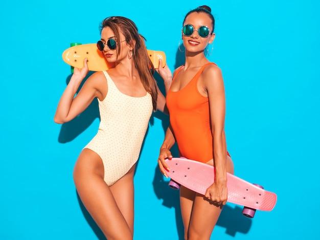Due belle donne sorridenti sexy in costumi da bagno colorati costumi da bagno estate. ragazze alla moda in occhiali da sole. modelle positive che si divertono con colorati penny skateboard. isolato Foto Gratuite