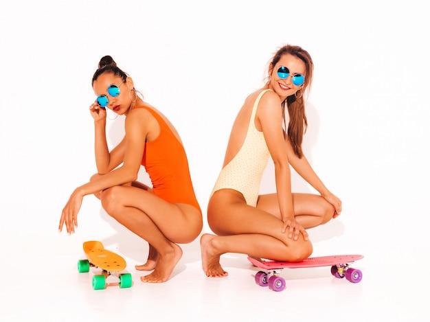 Due belle donne sorridenti sexy in costumi da bagno colorati costumi da bagno estate. ragazze alla moda in occhiali da sole. modelli positivi seduti sul pavimento con colorati penny skateboard. isolato Foto Gratuite