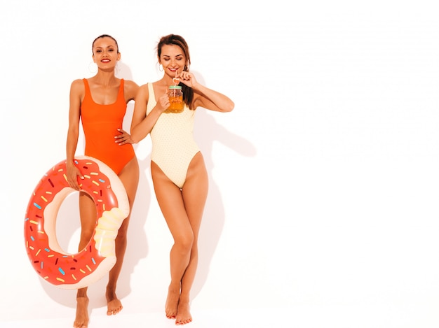 Due belle donne sorridenti sexy in costumi da bagno colorati costumi da bagno estate. ragazze isolate divertenti modelle che bevono cocktail freschi e bevande alcoliche con materasso gonfiabile a ciambella lilo Foto Gratuite