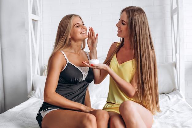 Due belle ragazze applicano la crema per il viso Foto Premium
