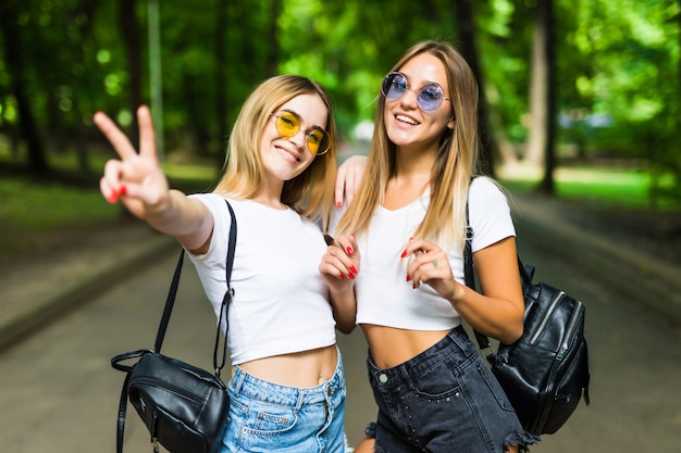 Due belle ragazze che camminano nel parco estivo terminano di parlare. amici che indossano pantaloncini di jeans e camicia alla moda, occhiali da sole, godendosi il giorno libero e divertirsi. Foto Gratuite