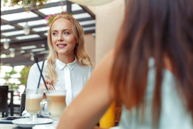Due belle ragazze che si siedono al tavolo nella caffetteria Foto Premium
