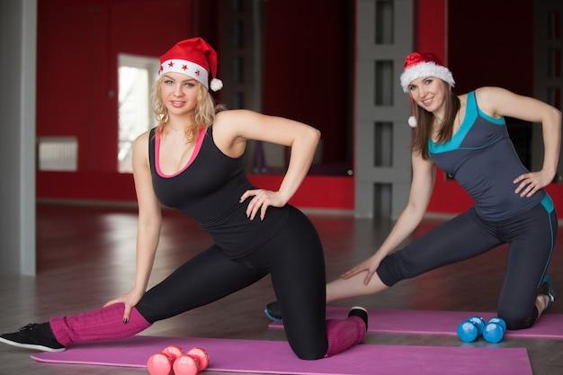 Due belle ragazze in cappelli di babbo natale esercitano sui tappetini nel centro fitness Foto Gratuite