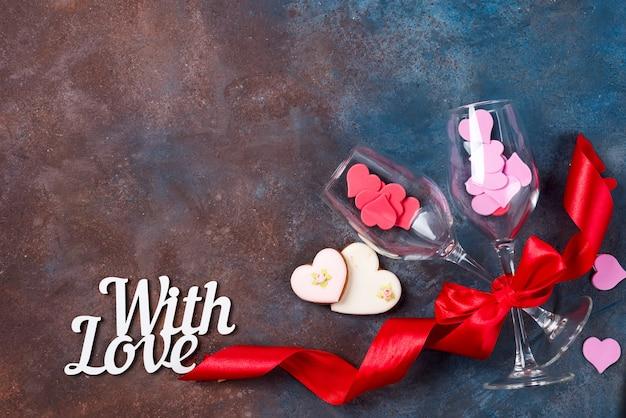 Due bicchiere di vino, cuori di biscotti su fondo di pietra. san valentino Foto Premium
