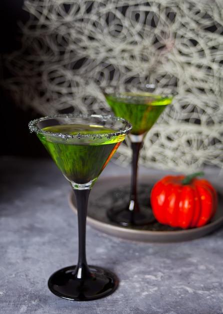 Due bicchieri con cocktail di zombie verdi per la festa di halloween su sfondo grigio Foto Premium