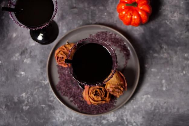 Due bicchieri con cocktail nero, rose secche, zucca per la festa di halloween su oscurità Foto Premium
