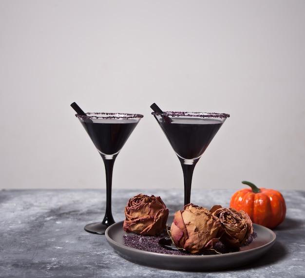 Due bicchieri con cocktail nero, rose secche, zucca per la festa di halloween Foto Premium