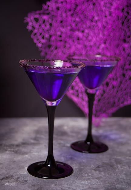 Due bicchieri con cocktail viola per la festa di halloween al buio Foto Premium