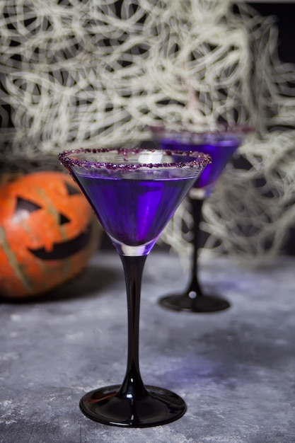 Due bicchieri con cocktail viola, zucca per la festa di halloween Foto Premium