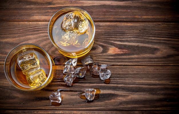 Due bicchieri con ghiaccio e whiskey Foto Premium