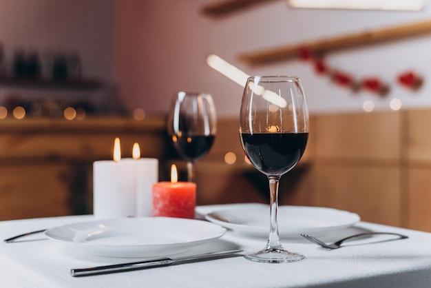 Due bicchieri con vino rosso e candele accese su un primo piano tavolo servito Foto Premium