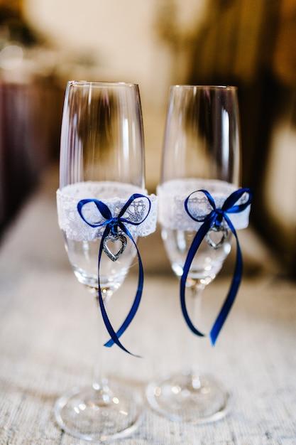 Due bicchieri da sposa sono decorati con nastri e cuori blu. Foto Premium