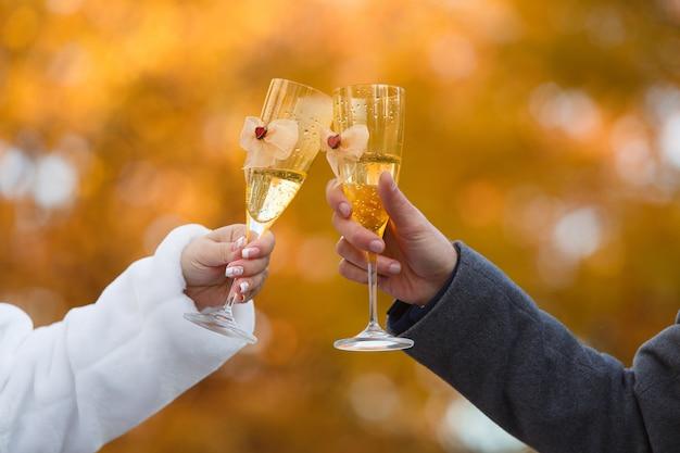 Due bicchieri decorati con uno champagne nelle mani della sposa e dello sposo. Foto Premium