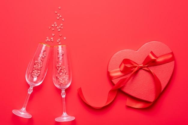 Due bicchieri di champagne con spruzzata di coriandoli a forma di cuore rosso su sfondo rosso. vista dall'alto, disteso, copia spazio. concetto di san valentino Foto Premium