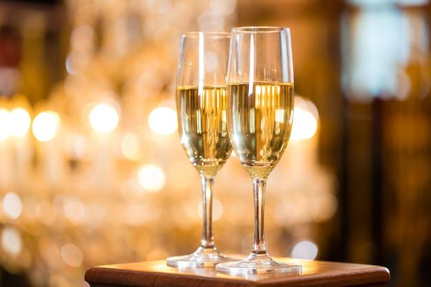 Due bicchieri di champagne in un raffinato ristorante, un grande lampadario è dentro Foto Premium