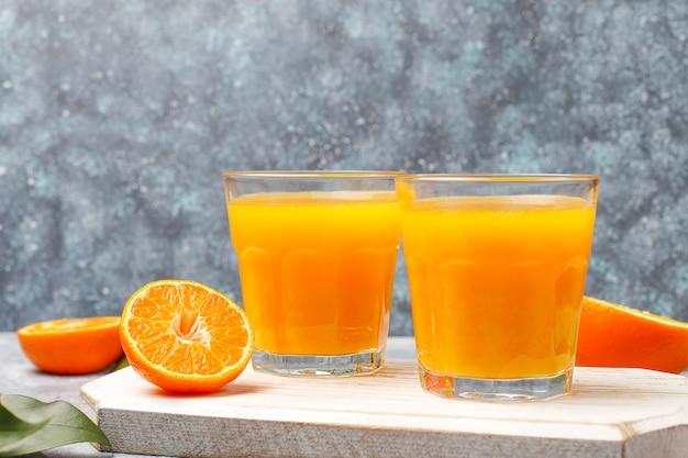 Due bicchieri di succo d'arancia fresco biologico con arance crude, mandarini Foto Gratuite