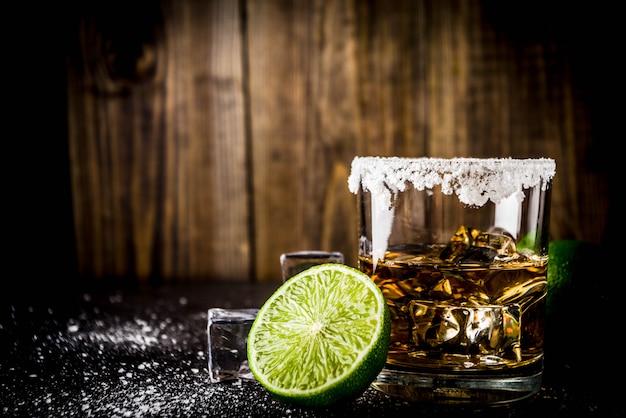 Due bicchieri di tequila sul tavolo scuro, con cubetti di ghiaccio, sale e lime Foto Premium