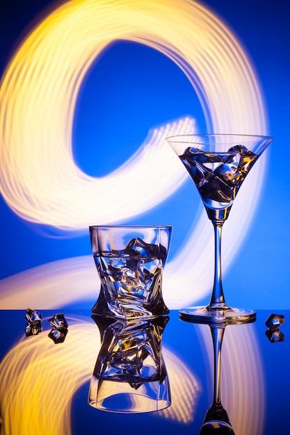 Due bicchieri di un cocktail di ghiaccio, contro l'azzurro di bellissimi effetti di luce. Foto Premium