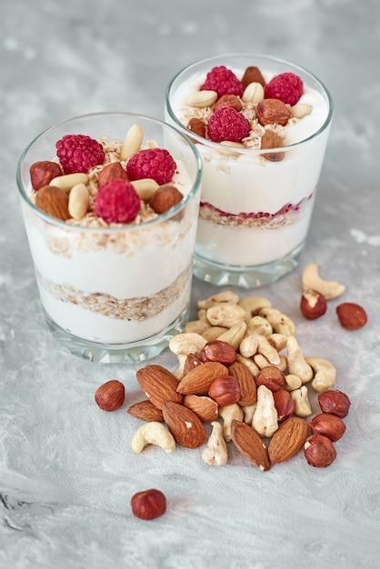 Due bicchieri di yogurt greco granola con lamponi Foto Premium