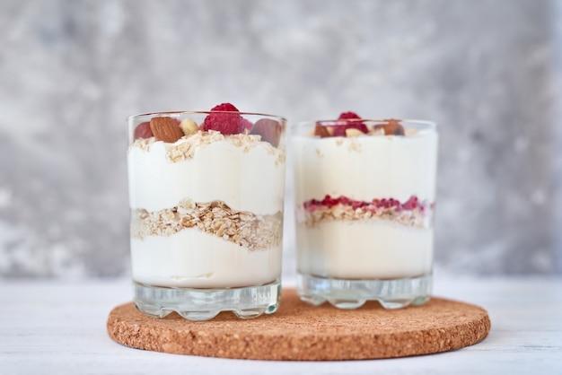 Due bicchieri di yogurt greco muesli con lamponi, fiocchi d'avena e noci. alimentazione sana Foto Premium