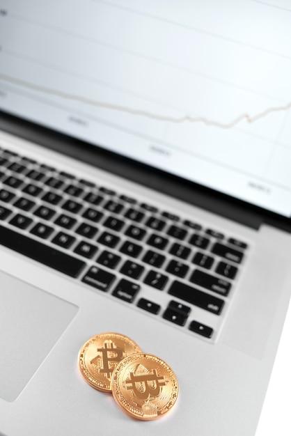 Due bitcoin d'oro posizionati sul portatile d'argento con grafico finanziario sul suo schermo Foto Premium