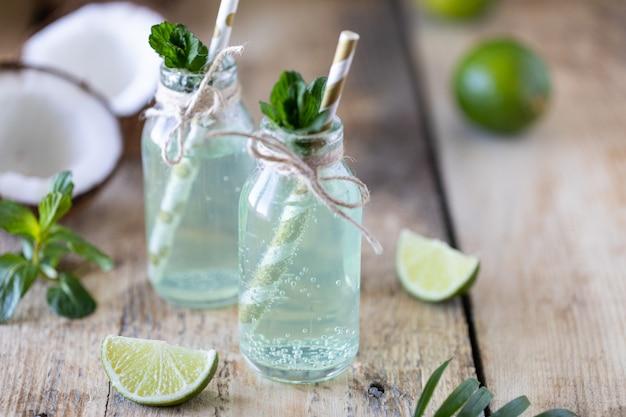 Due bottiglie di acqua di cocco con menta e lime su un tavolo di legno. bevanda vegetariana. mojito. copia spazio Foto Premium