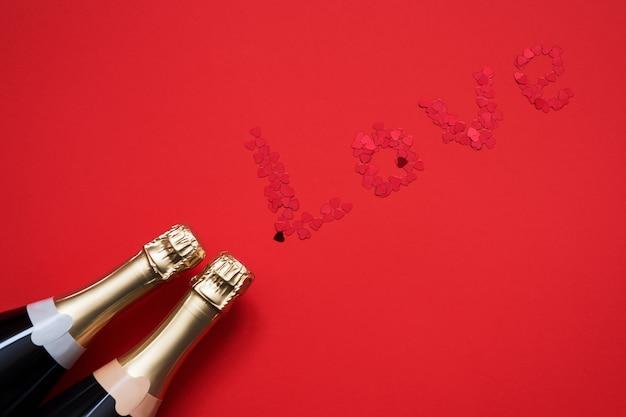 Due bottiglie di champagne con i cuori hanno modellato i coriandoli che formano la parola amore su fondo rosso. Foto Premium