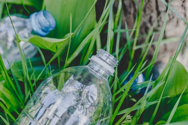 Due bottiglie di plastica si trovano sull'erba a terra nella foresta Foto Premium