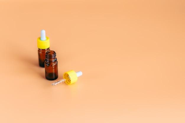 Due bottiglie di siero di vetro contagocce su sfondo arancione Foto Premium
