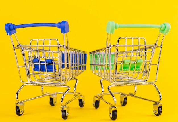 Due carrello della spesa verde e blu in miniatura su sfondo giallo Foto Gratuite