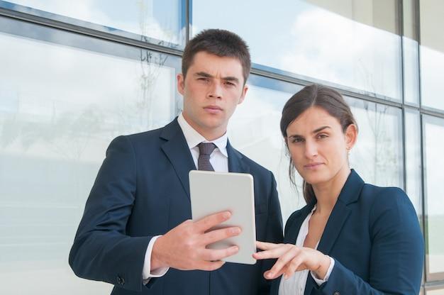 Due colleghe seri che utilizzano compressa durante la pausa di lavoro all'aperto Foto Gratuite