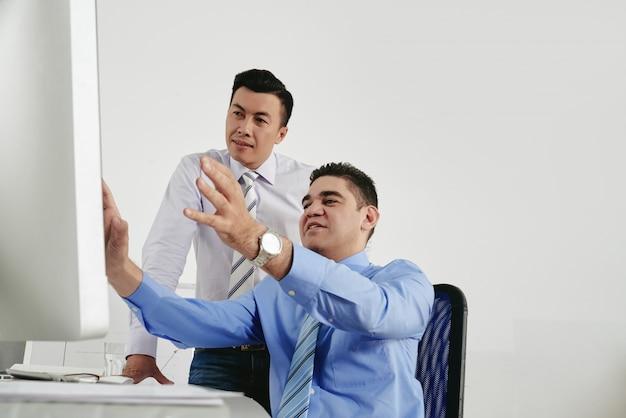 Due colleghi di brainstorming in ufficio guardando lo schermo del computer Foto Gratuite