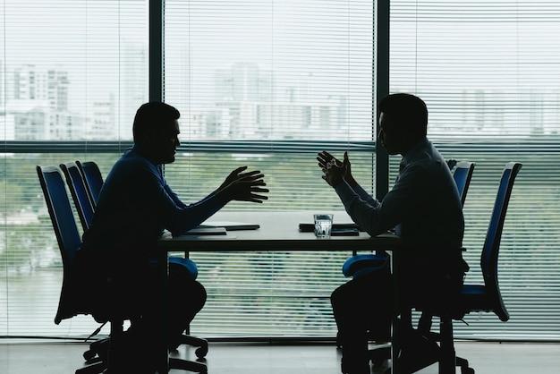 Due contorni umani contro la finestra dell'ufficio con le imposte seduti uno di fronte all'altro e in trattativa Foto Gratuite