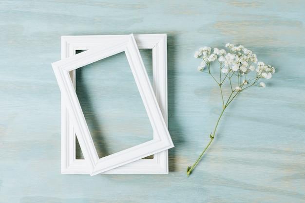 Due cornici di confine bianco con fiore baby's-breath sullo sfondo in legno texture Foto Gratuite