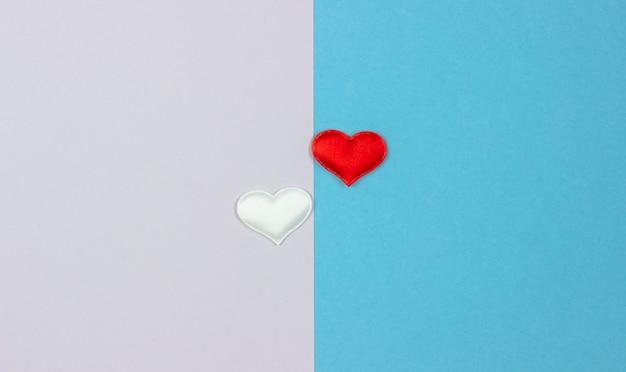Due cuori bianchi e rossi su due lati dello sfondo. Foto Premium