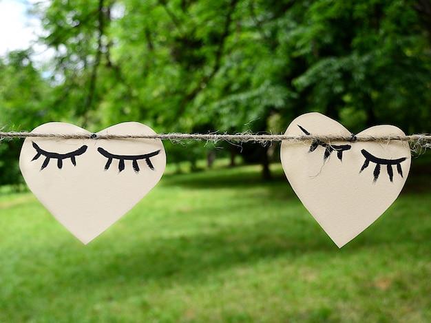 Due cuori di carta che appendono su una corda, concetto di san valentino. Foto Premium