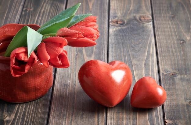 Due cuori di pietra e mazzo di tulipani rossi su fondo di legno Foto Premium