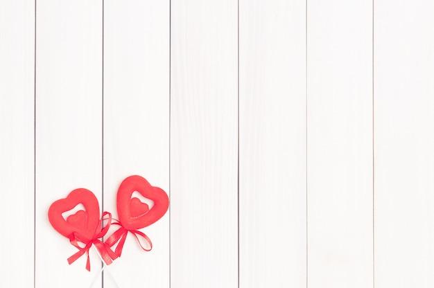 Due cuori rossi su bastoncini di legno. Foto Premium