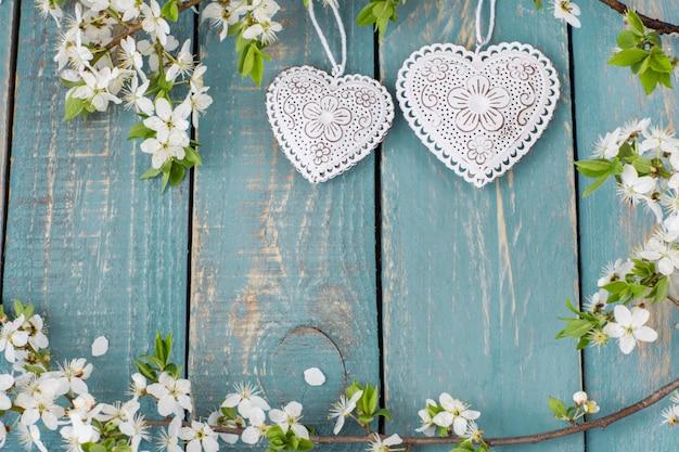 Due cuori traforati e rami di ciliegio in fiore Foto Premium