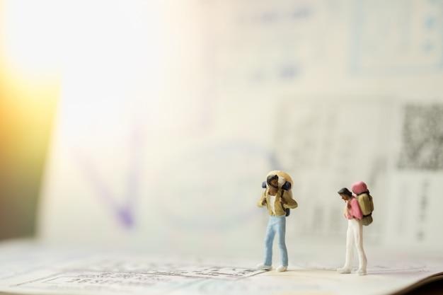 Due di mini personaggi in miniatura con zaino in piedi e parlando sul passaporto con francobolli di immigrazione Foto Premium